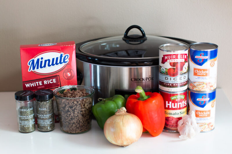 Cans of food, vegetables, minute rice, beef and seasonings in front of a slow cooker