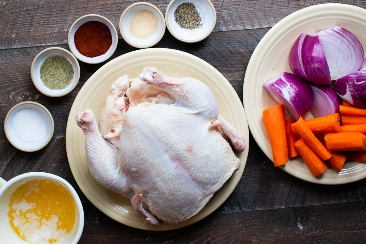 raw chicken, seasonings, melted butter and vegetables on a wooden table.