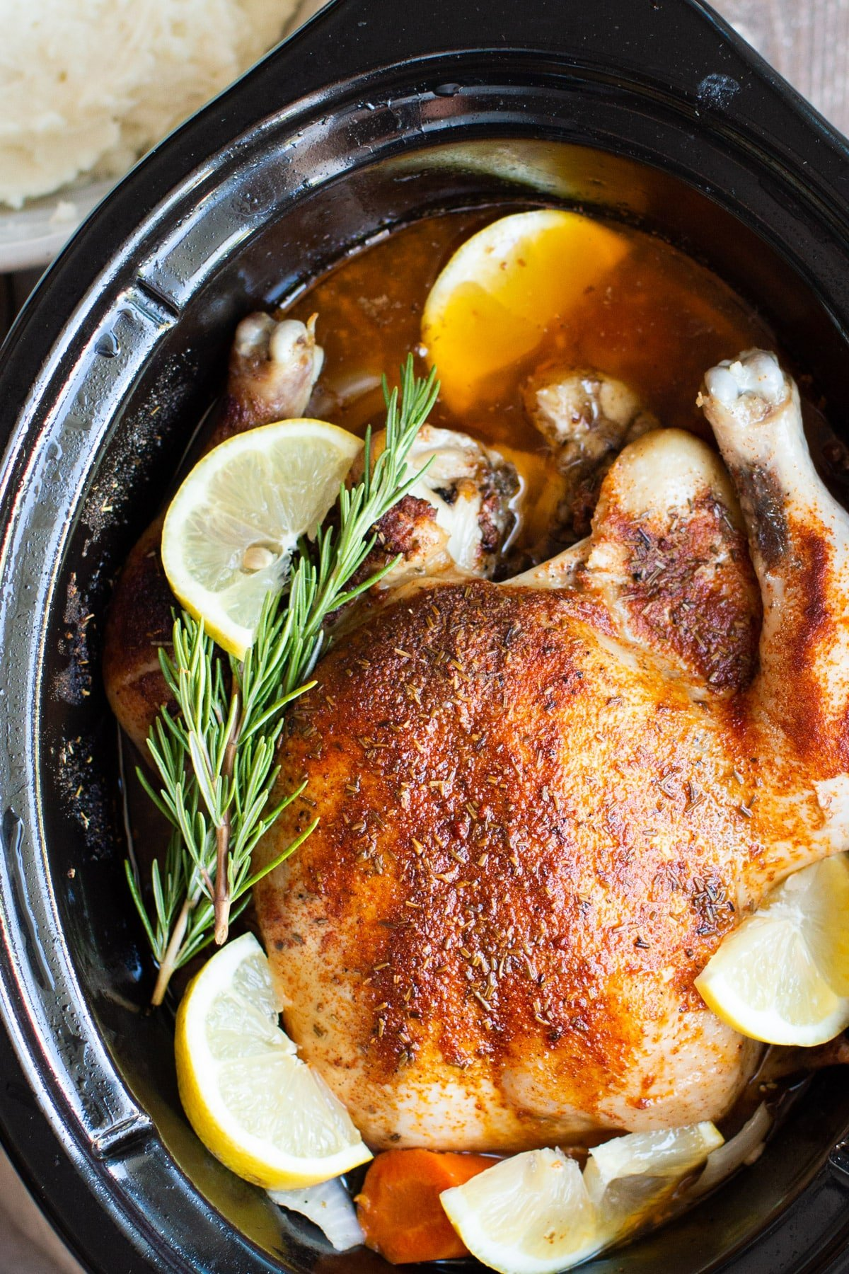 close up of a cooked whole chicken with lemon and rosemary in a slow cooker