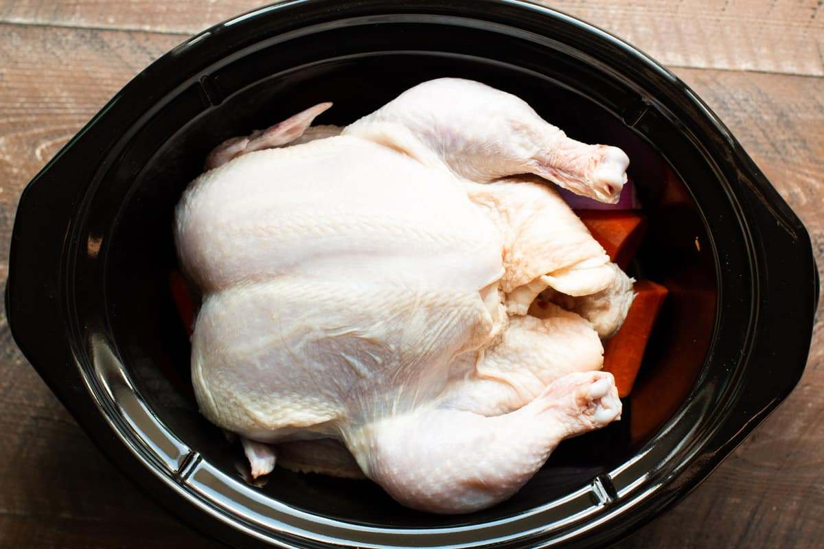 whole chicken on top of vegetables in a slow cooker.