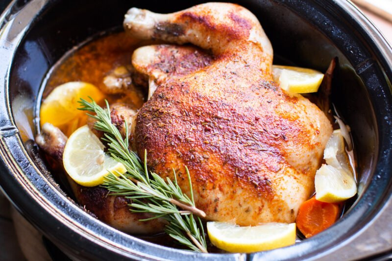 whole cooked chicken in a slow cooker with lemons
