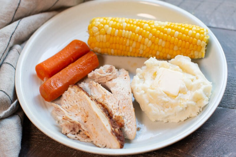 sliced chicken, mashed potatoes, corn and carrots on plate