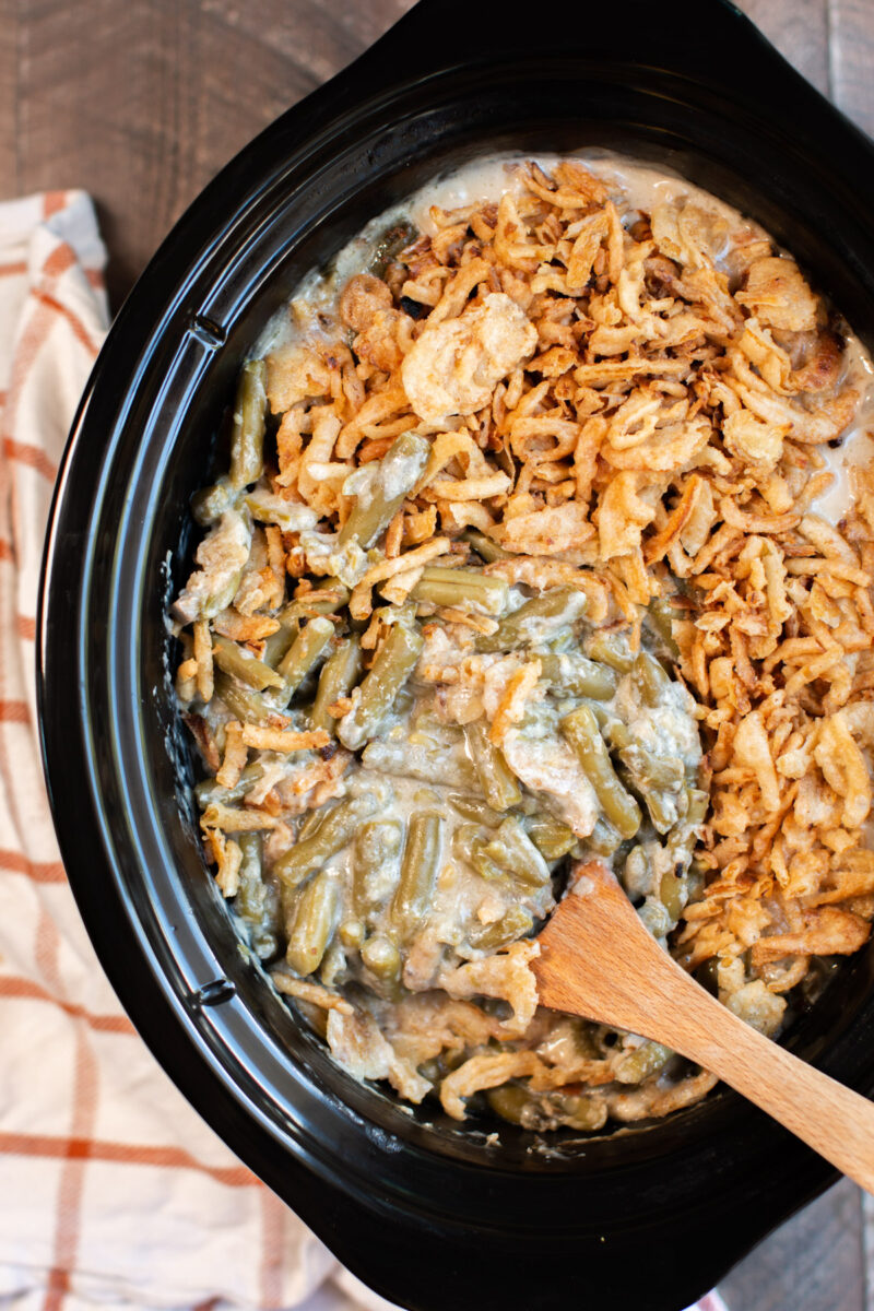 close up of green bean casserole with a spoon in it.