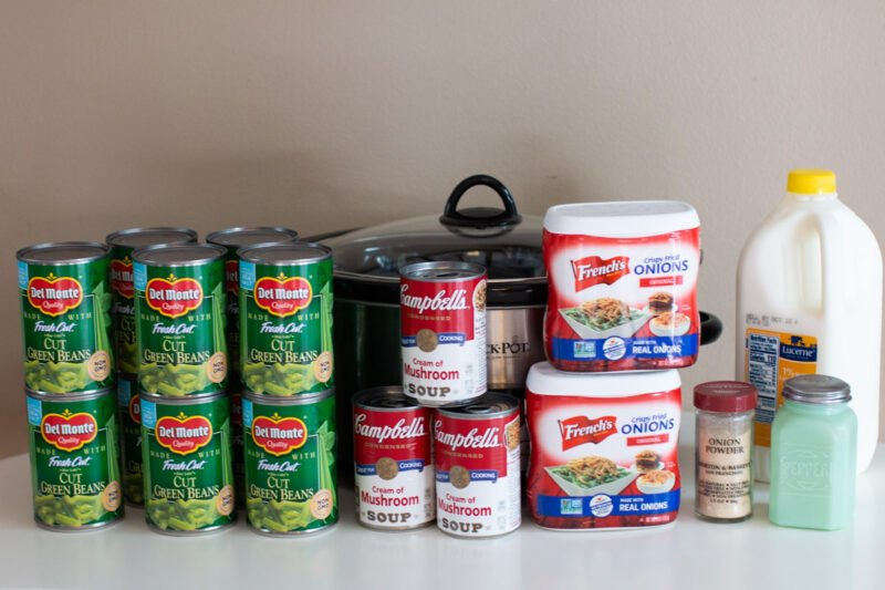 canned green beans, cream of mushroom soup, french fried onions, milk in front of slow cooker.