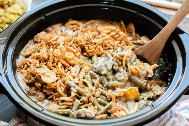 close up image of green beans in sauce with French fried onions on top.