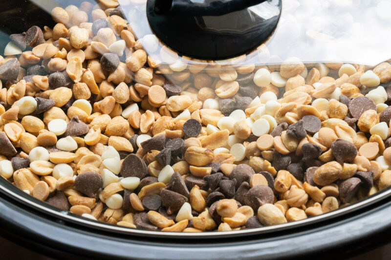 lid on slow cooker with peanuts and chocolate chips in it