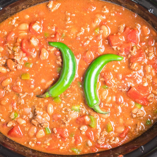 chili with 2 serrano peppers on top in slow cooker