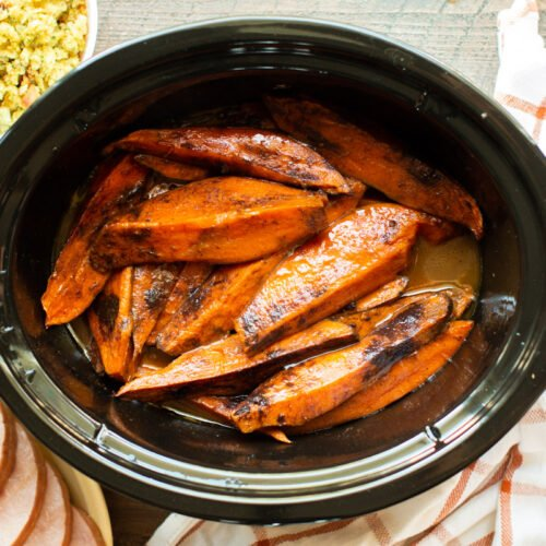 sweet potato wedges done cooking in slow cooker with cinnamon on top.