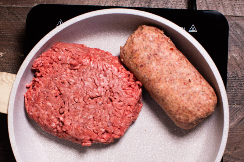 skillet with a pound of ground beef and a pound of hot sausage