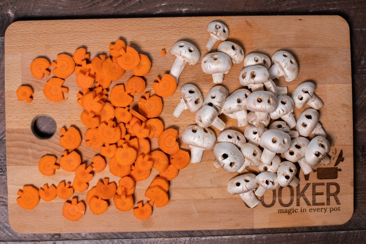 cutting board with cut carrots shaped like pumpkins and mushrooms cut like skulls
