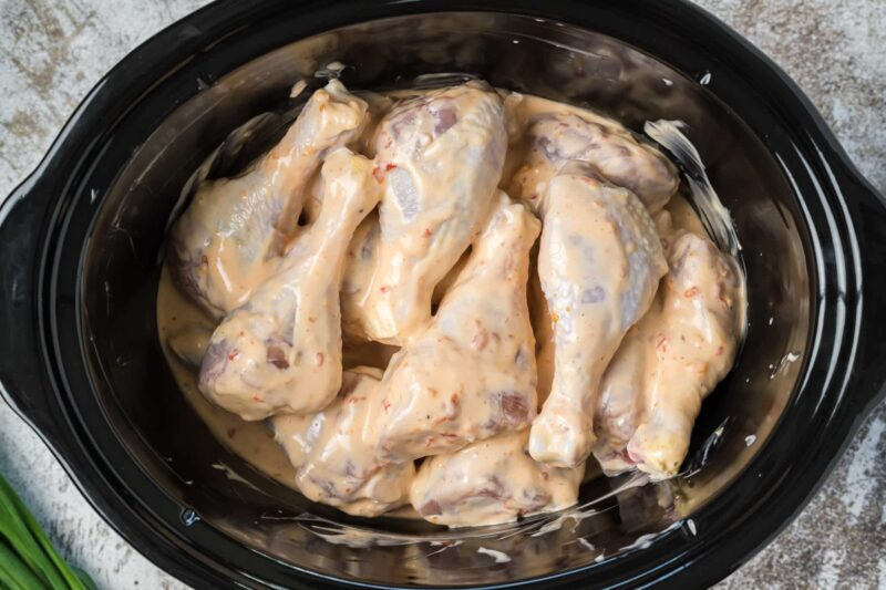 drumsticks in bang bang sauce in slow cooker before cooking.