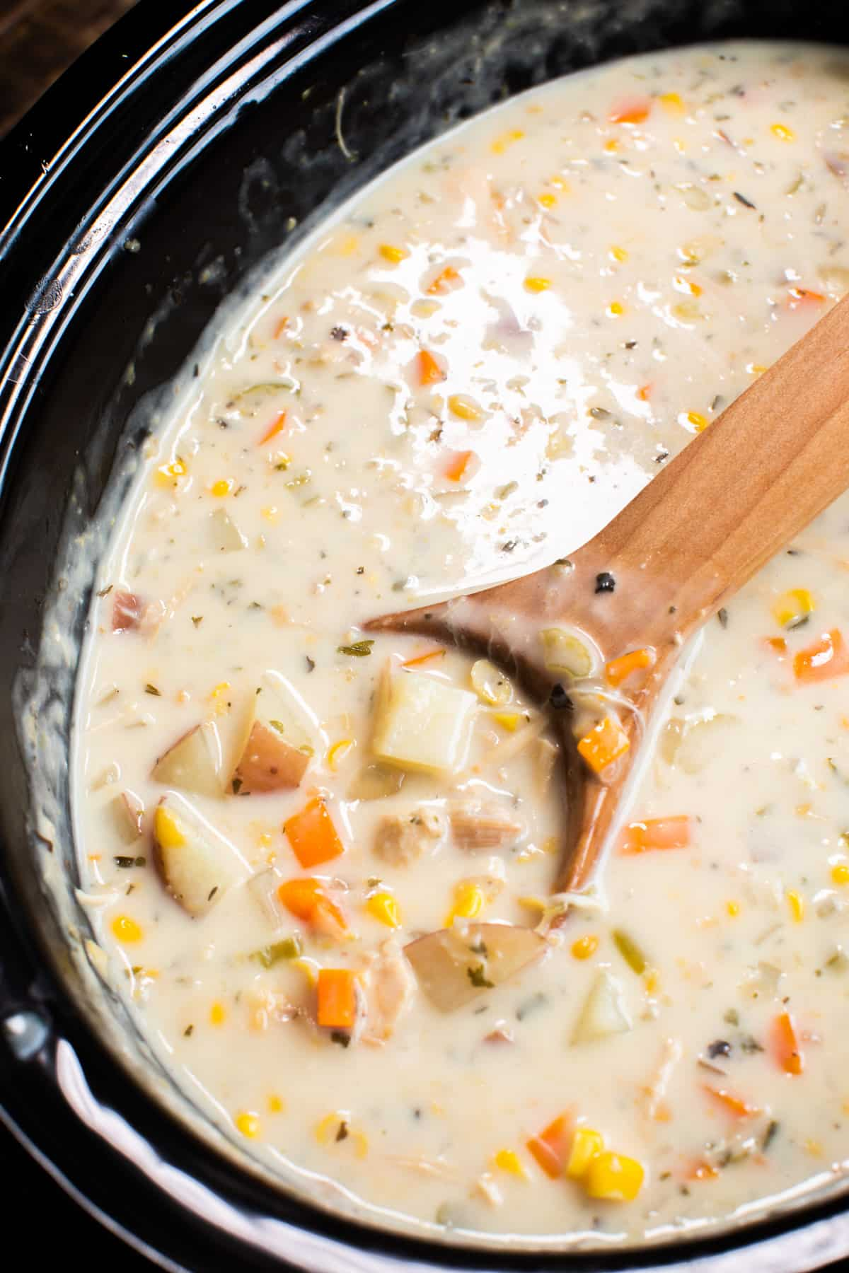 close up of turkey chowder on wooden spoon.