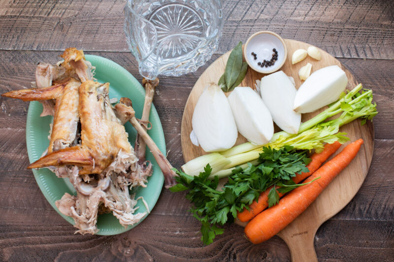 turkey pieces, vegetables, bay leaves, peppercorns and water on a table.