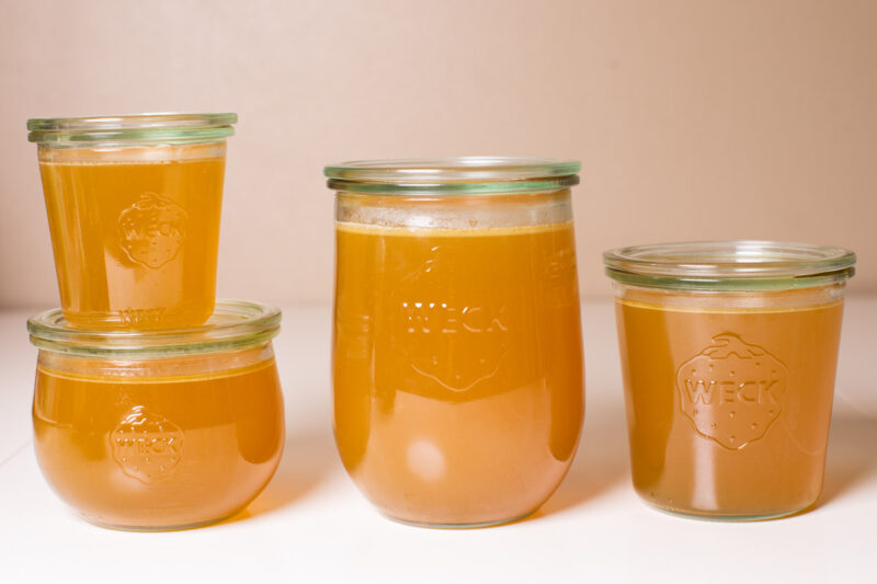 4 jars of turkey stock on a white table.