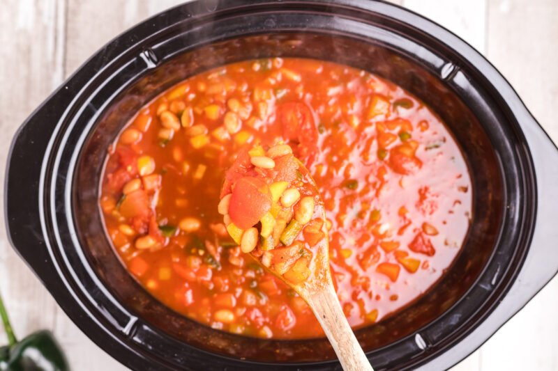 cooked vegetarian chili in slow cooker and on wooden spoon.