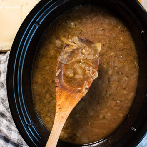 close up of french onion soup on wooden spon