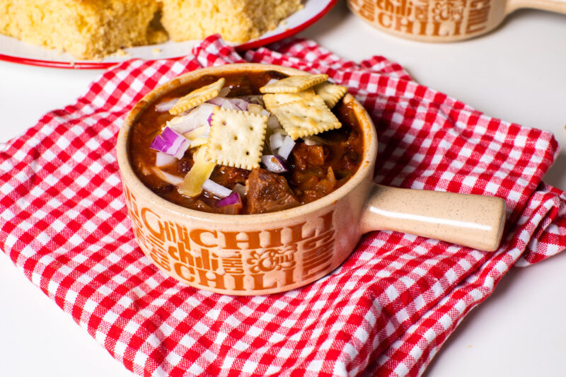 bowl of prime rib chili with crackers, cheese and onions on top.