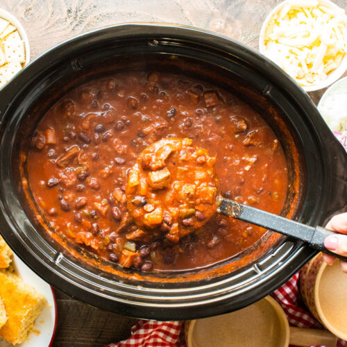 prime rib chili being scooped out of slow cooker