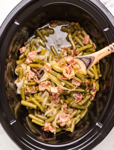 green beans and bacon is sauce in slow cooker and on wooden spoon