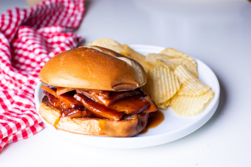 barbecue ham on bun with chips on side
