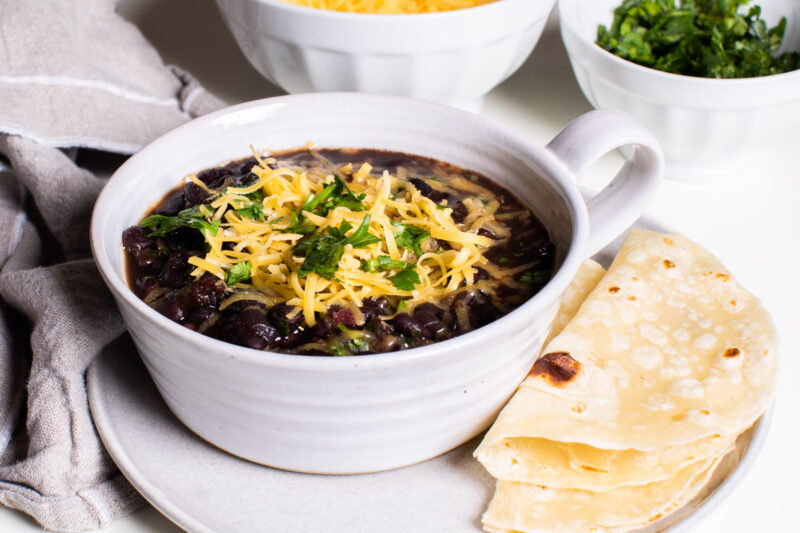 white bowl with black bean soup in it. Topped with cheddar cheese and cilantro.