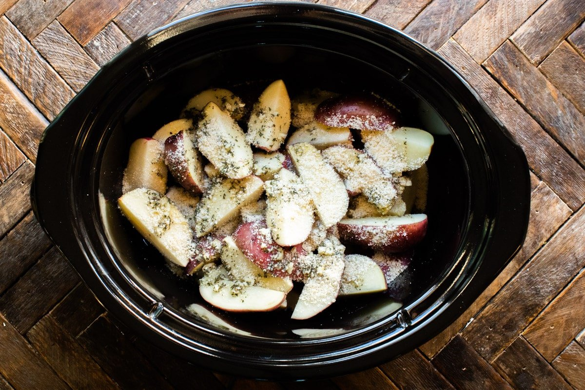 red potatoes with garlic, seasonings and parmesan in slow cooker