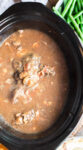 close up of venison roast in mushroom bacon gravy in slow cooker