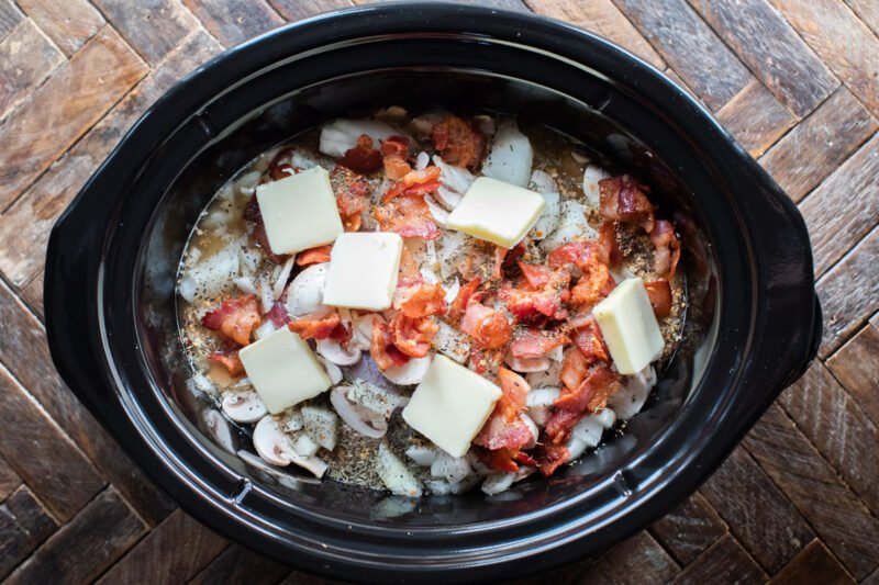 venison roast in slow cooker with bacon, onion, butter and onion on top, before cooking.