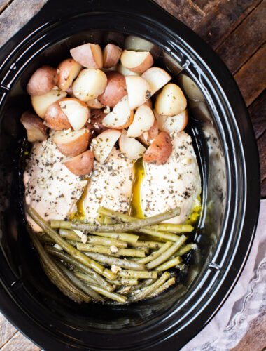 close up photo of chicken, potatoes and green beans in slow cooker