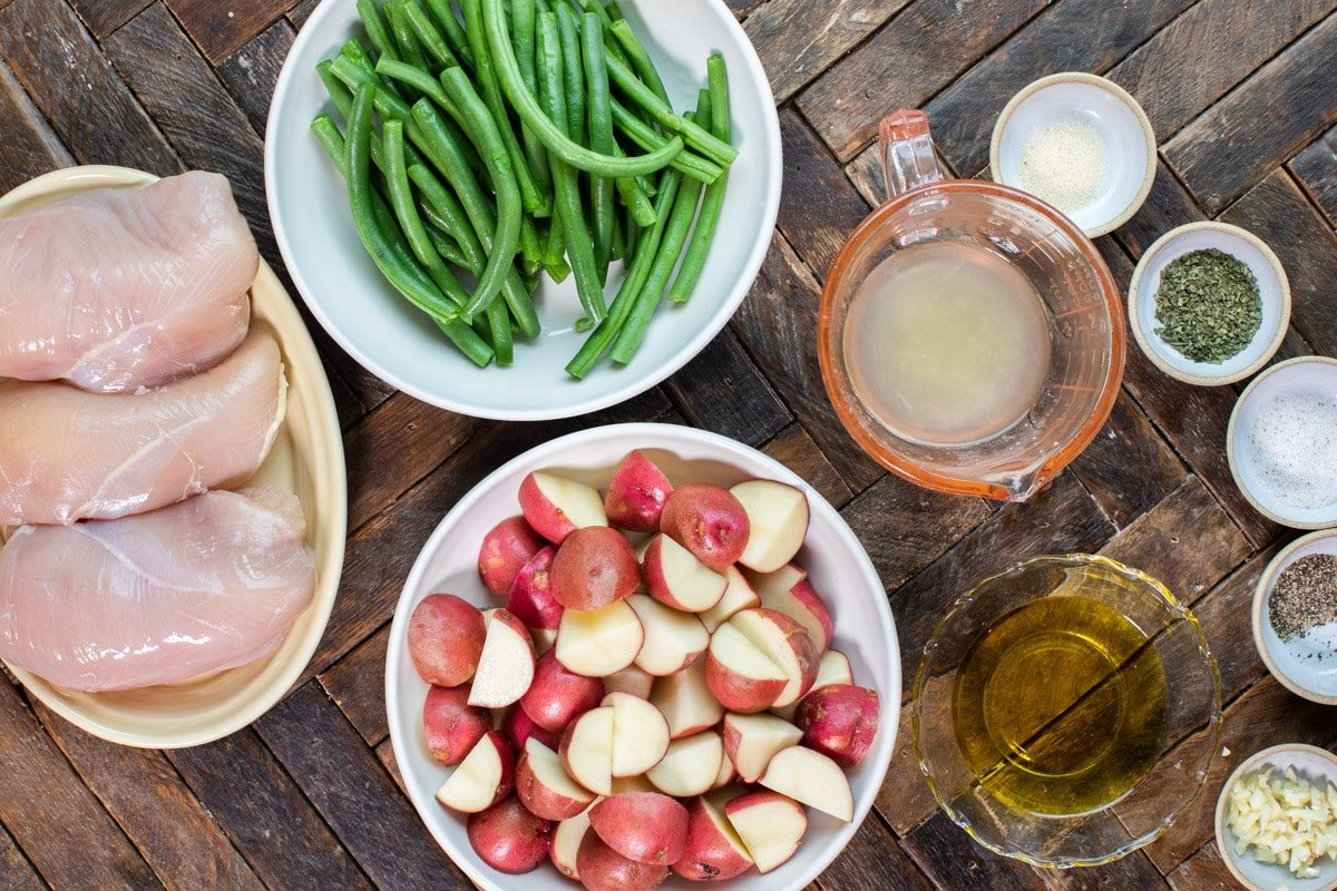 ingredients for chicken and vegetable slow cooker meal on wooden table