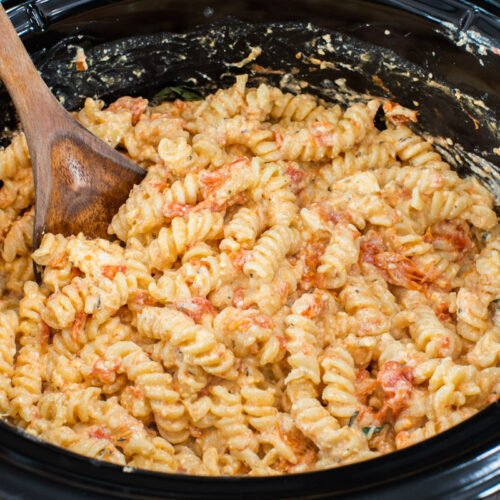 feta tomato pasta in slow cooker with wooden spoon in it