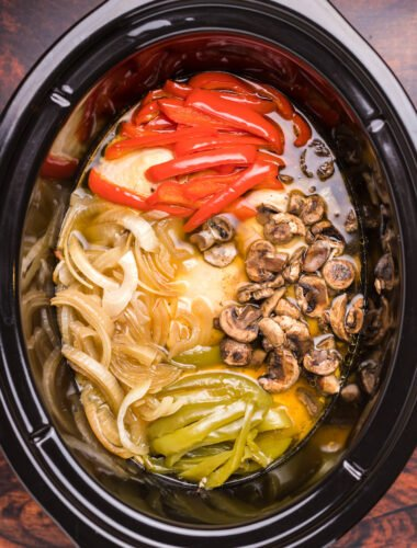 image of chicken, bell peppers, onions and mushrooms in slow cooker