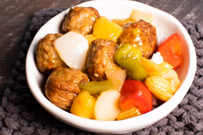 sweet and sour meatballs in bowl over rice