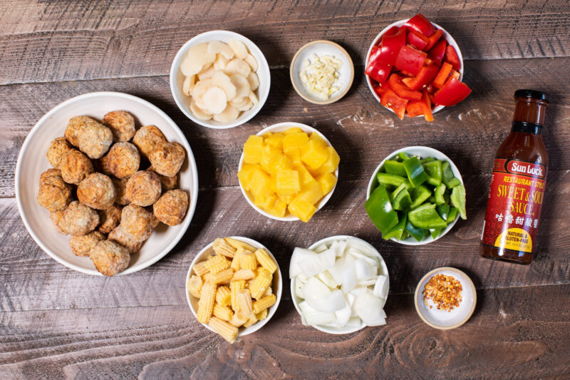 ingredients for sweet and sour meatballs in bowl on wooden table