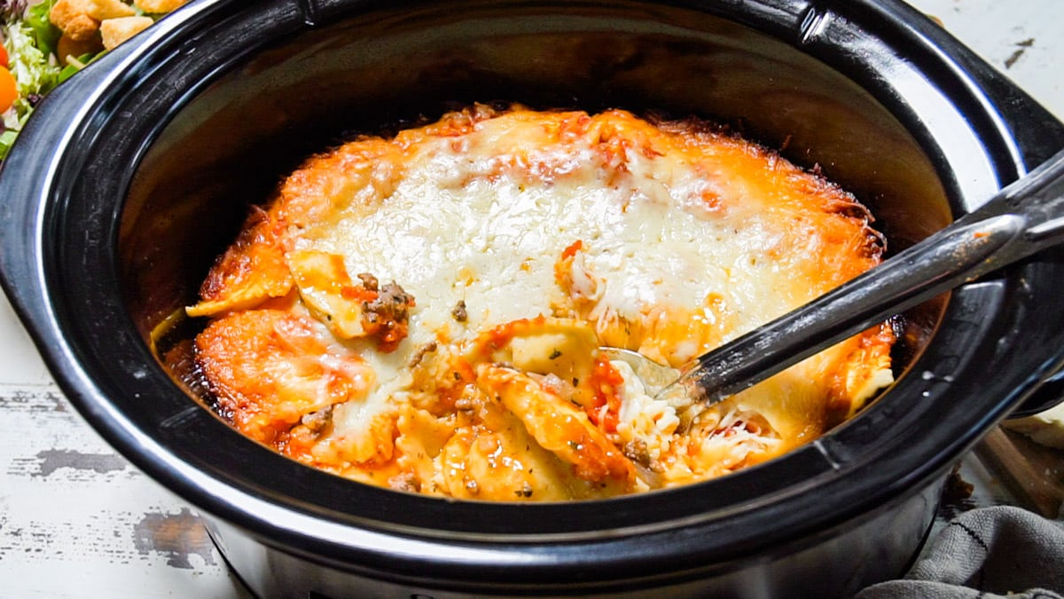 close up of ravioli in slow cooker with metal spoon in it.