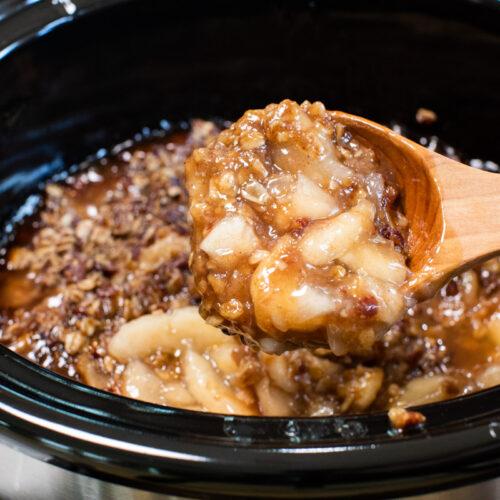 scoop of apple crisp coming from slow cooker