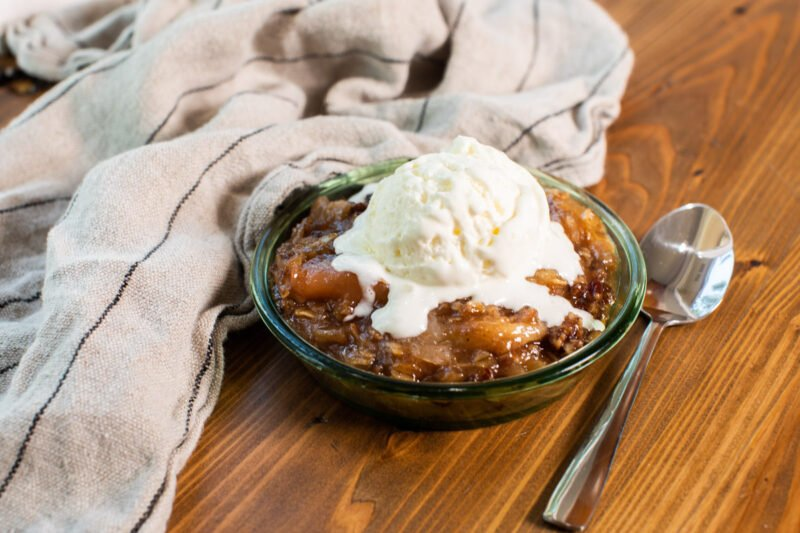 apple crisp in bowl with ice cream on top.