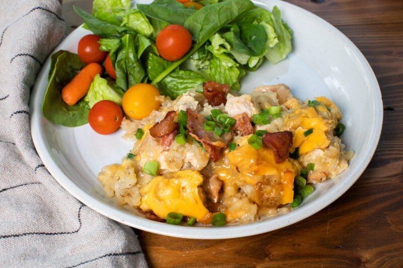 serving of chicken tater tot casserole on plate with salad