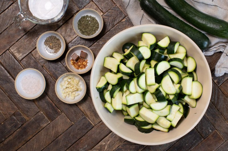 sliced zucchini in bowl with spices on the side