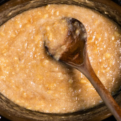 close up of banana jam in slow cooker with wooden spoon in it.