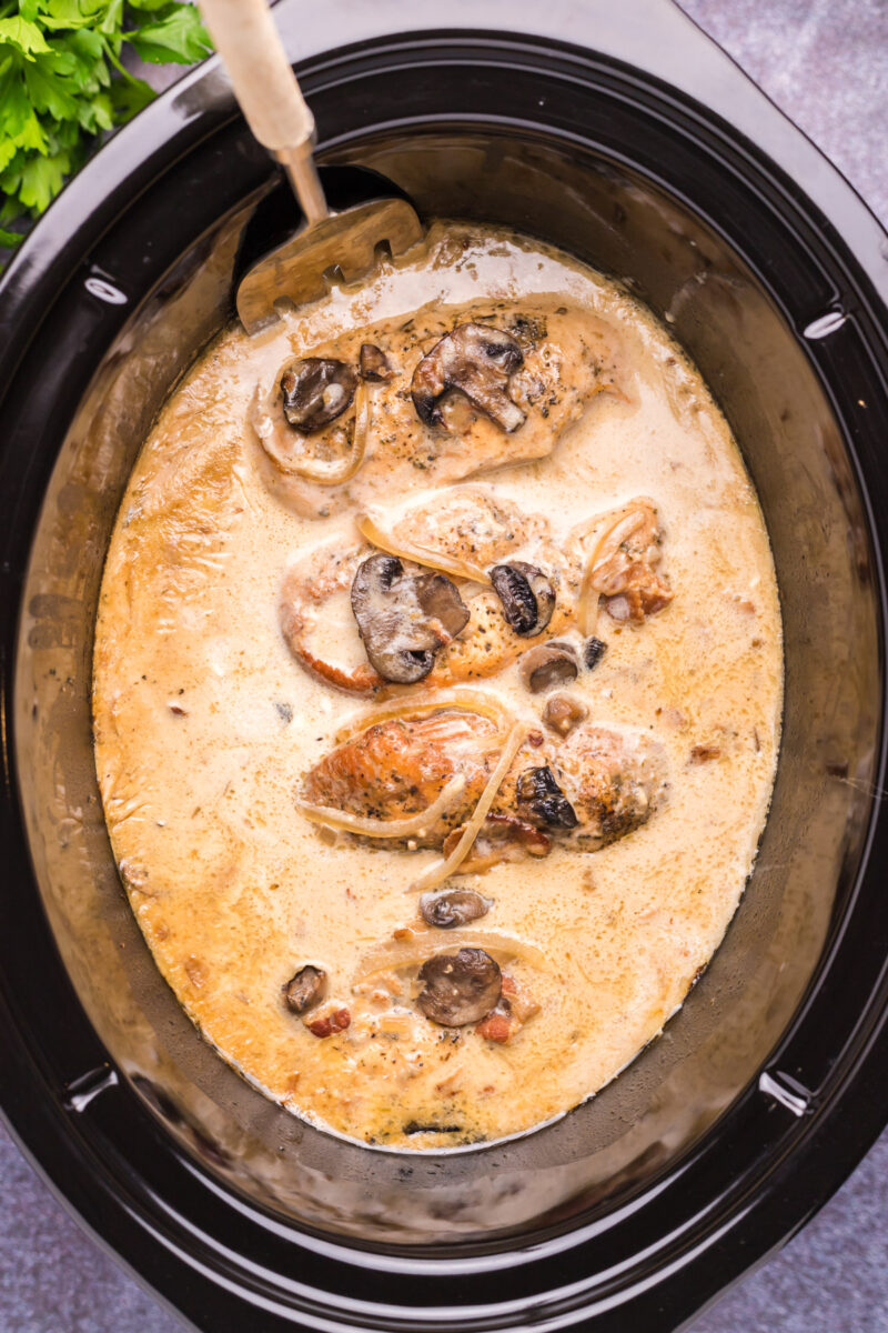 close up of chicken marsala in slow cooker with spoon in it.