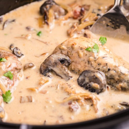 close up of chicken marsala in slow cooker with parsely on top.