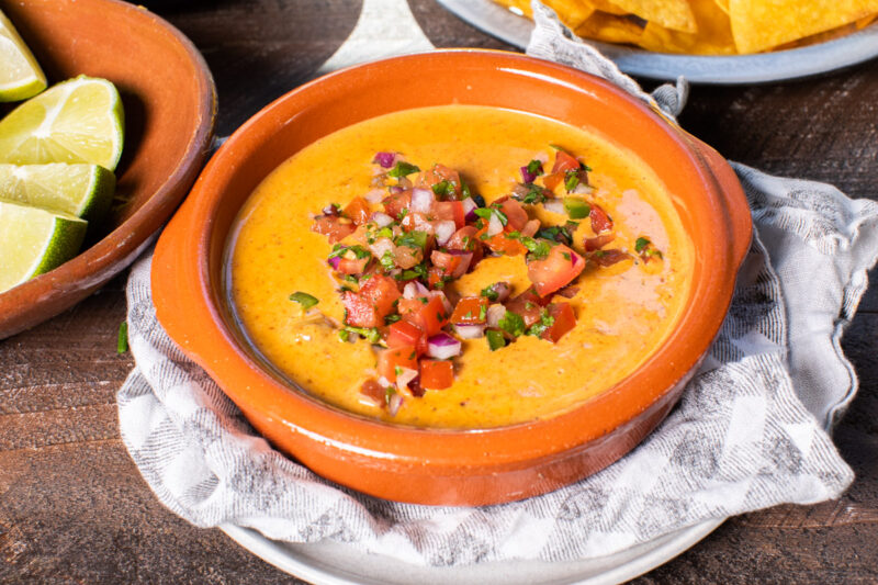 brown bowl with chili cheese dip in it with salsa on top.