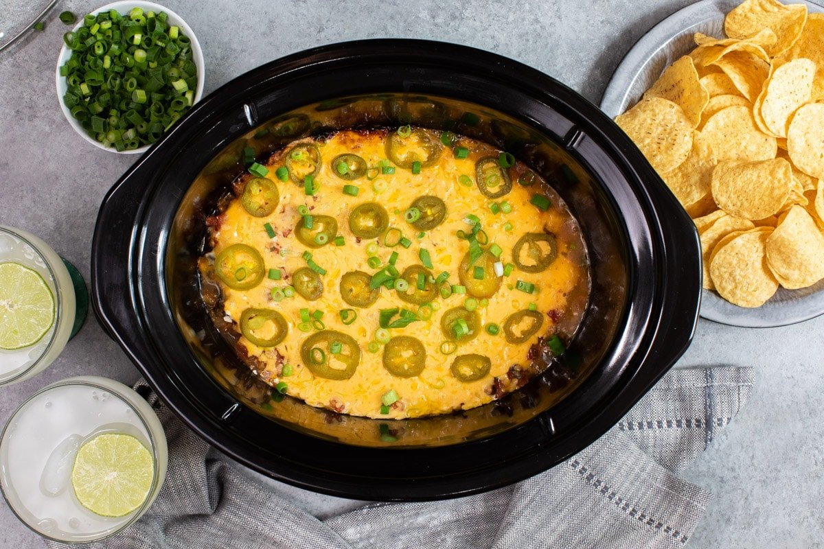 7 layer bean dip done cooking in slow cooker with jalepenos and onions on top.
