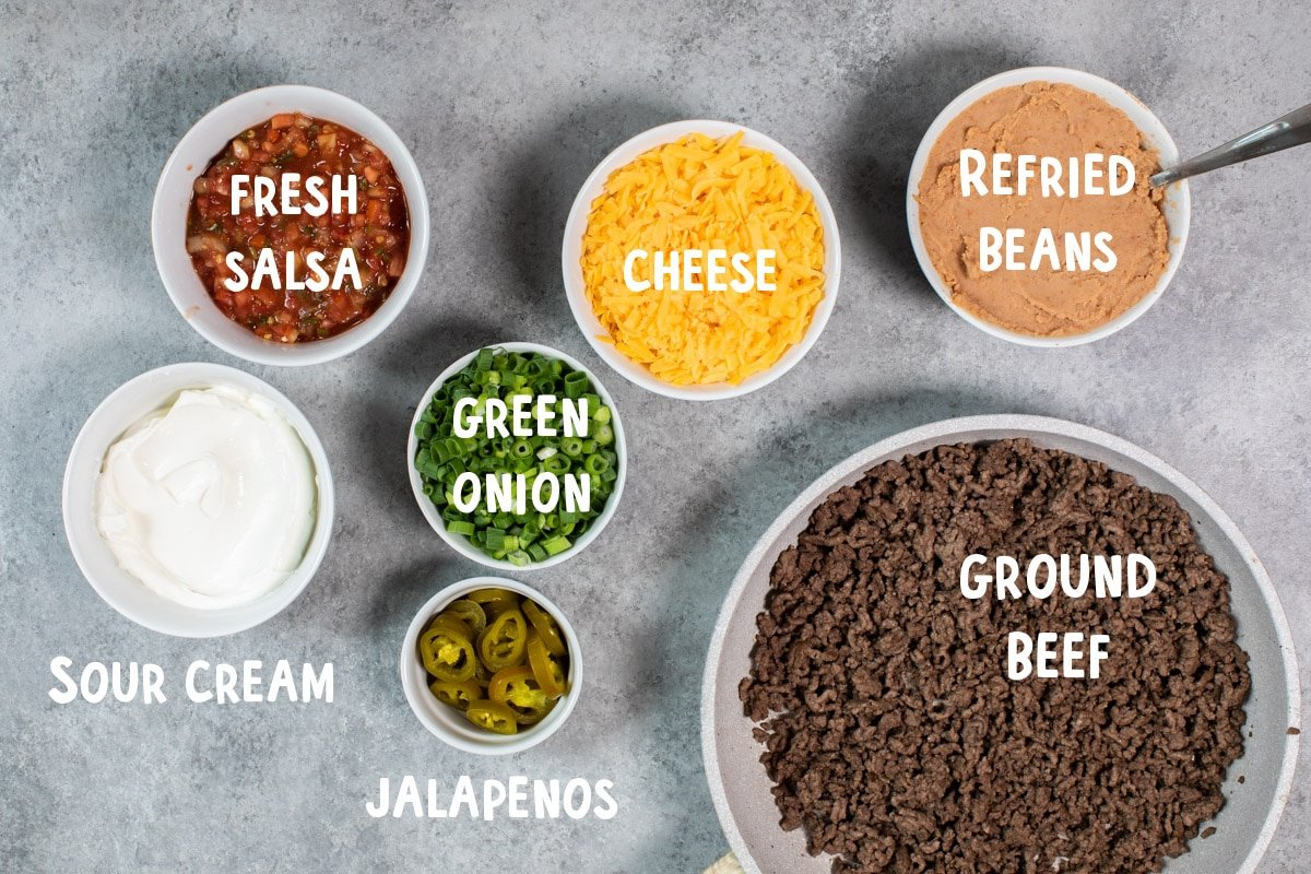 ingredients for 7 layer bean dip on table. With text overlay