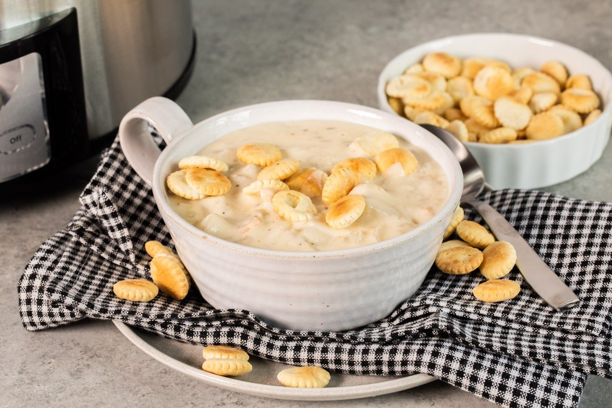 clam chowder in white bowl with oyster crackers on top