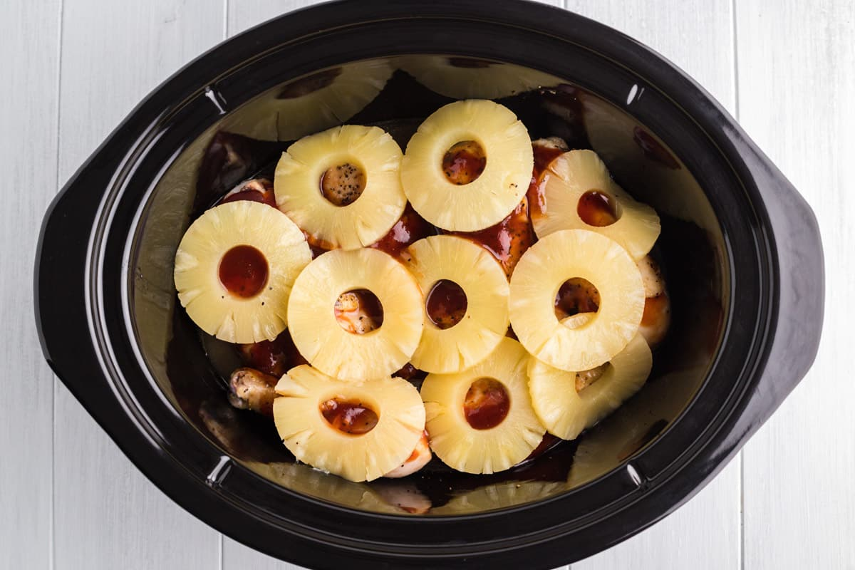 Pineapple rings on top of chicken and bbq sauce in slow cooker
