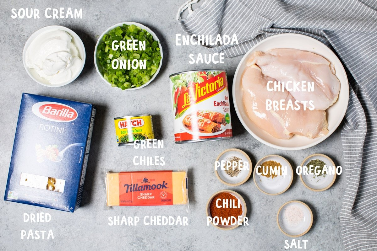 ingredients for enchilada pasta on table with text over lay of ingredient names