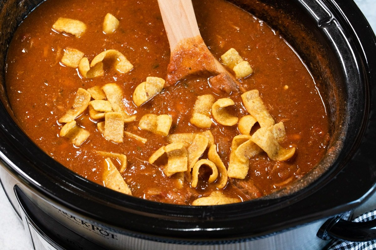 side view of steakhouse style chili in slow cooker with frito chips on top