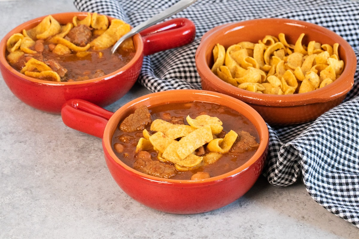 chili in red bowl with fritos on top.
